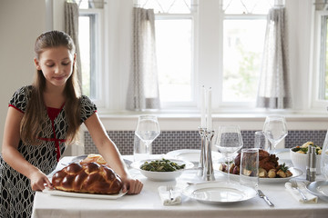 Girl placing challah bread on a table for Shabbat meal