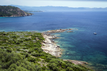 green coastline, azure sea between rocks in the mountains on the island of Corsica