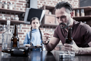 Chronic depression. Cheerless serious depressed man holding a bottle and looking at it while drinking alcohol at home