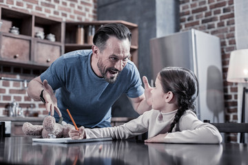 Angry father. Aggressive emotional brutal man looking at his child and shouting at her while being angry