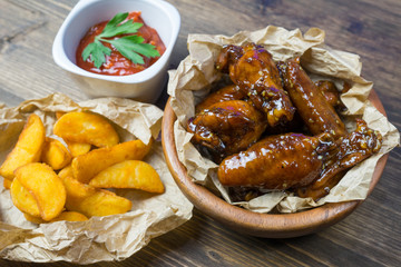 Chicken wings in a fragrant and pungent sauce with sesame seeds. A glass of fresh cold beer and fried potatoes with rustic tomato sauce from fresh tomatoes and herbs