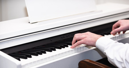 Music performers hands with white cuffs playing piano.