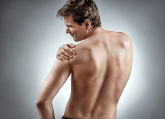 Man suffering from a shoulder injury. Photo of man holding his injured shoulder on grey background. Medical concept.