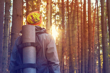 Man with backpack, traveler in the woods looking at sun. Forest, hiking, journey. Toned