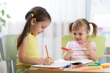 happy children drawing in nursery room
