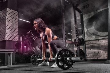 Young beautiful muscular girl sportsman bodybuilder doing exercises in a modern gym using a barbell, against a dark background.