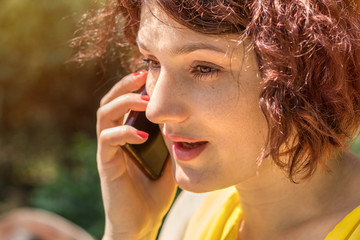 Young redhead woman talking on the phone outdoors on a sunny day.  Portrait redhead woman on the phone with copy space