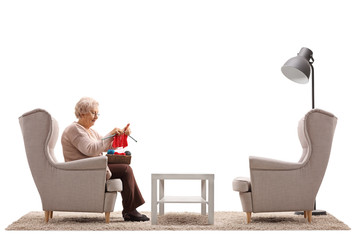 Lonely elderly woman sitting in an armchair and knitting