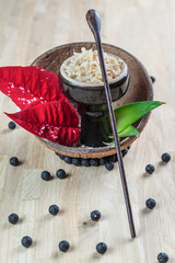 Shisha coconut in glossy black cup on a plate with opened coconut