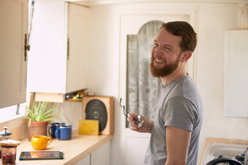 Smiling man standing in the kitchen while holding eyeglasses