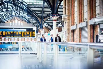 Three mature men at train station, walking together