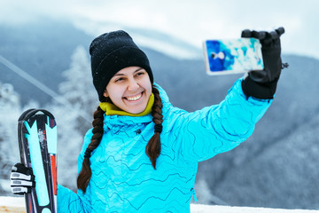 woman stands with ski  on the top of the hill and makes selfie