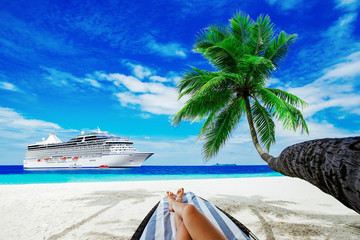 Wall Mural - Woman on sunbed under palm tree. Cruise liner on sea. Travel background