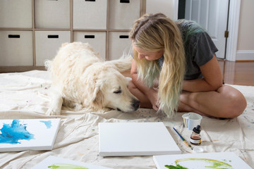 Female artist sitting on dust sheet petting dog in studio