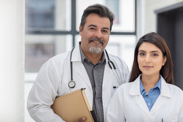 Portrait of male and female doctor standing in hospital