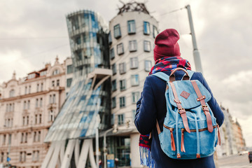 Woman tourist in a coat with a backpack travels in the Prague and looking at famous Dancing House