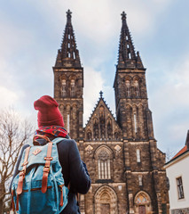 Pretty young female tourist with backpack looking at majestic Basilica of St. Peter and Paul in Prague