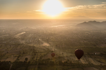 Aerial sunrise view flying over the temple and pagoda field at Bagan, Myanmar as seen from a hot air balloon flight