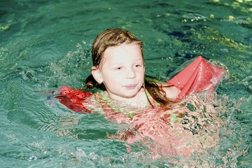 Small blond girl with armband floats in swimming pool. Child learns to swimm.