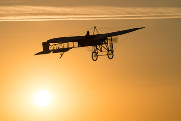 Old vintage airplane flying in an orange sky at sunset