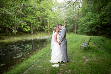 happy bride and groom by a pond