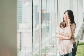Happy beautiful Asian woman talking with her friend via smartphone mobile in modern office building