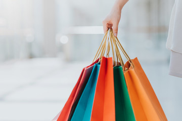Close up shot of young woman carrying colorful shopping bags while walking in shopping mall
