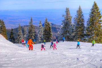 Adults and children practicing ski sport on the slope in winter holiday in one of the most attractive place of Europe - Poiana Brasov, Romania,
