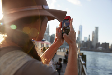 Tourist Taking Photo Of Manhattan Skyline On Mobile Phone