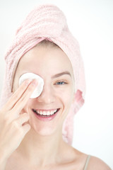 Facials. Girl with towel on head wipes clean the skin with a sponge on white background