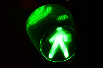 Night photo of a traffic light for pedestrians, which lights up in green Fotomurales
