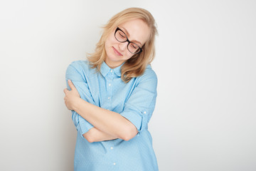 The love of oneself. Girl on a white background in a blue shirt and glasses hugging his
