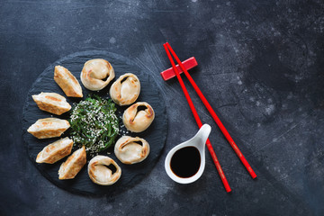 Stone slate with pan fried asian dumplings served with chuka salad. Flat-lay on a dark scratched metal background with space, horizontal shot