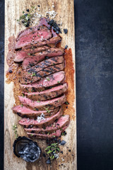 Traditional American barbecue dry aged flank steak sliced as close-up on a wooden board