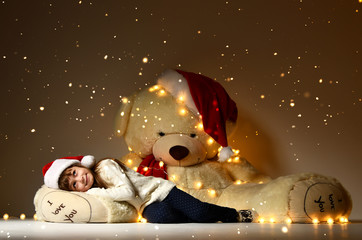 Young  girl sleeping with big soft teddy bear toy in christmas santa red hat looking up on shining light