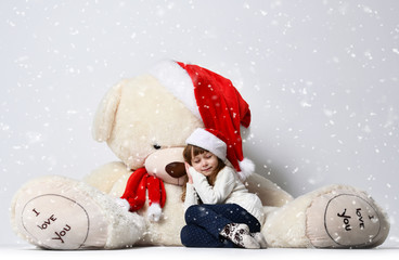 Young  girl sitting and sleeping with big soft teddy bear toy in christmas santa red hat under heavy snow