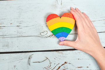 LGBT concept. Hand on wooden background holding heart rainbow colors