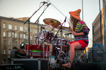 Shot of a girl with colorful clothes and orange hat playing drums on stage during music festival in summer. Band performing their songs