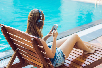 Happy smartphone woman relaxing near swimming pool listening with earbuds to streaming music. Beautiful girl using her mobile phone app 4g data to play songs while relaxing on summer luxury vacations
