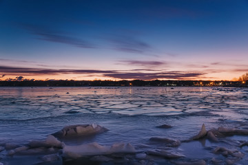 ice on the water near the shore. broken ice on the lake.   floating of ice. lights of the city in the distance