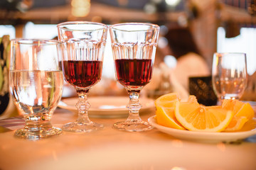 A table for two with red wine, water and lemon