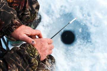 fisherman with a fishing rod sits on a river in the winter