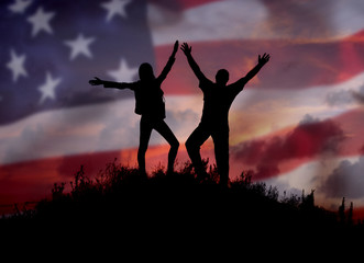 Two people against the American flag Full length silhouette of a happy couple stand together on top of a mountain with their hands up, Man and woman on top of a mountain of freedom.Democracy
