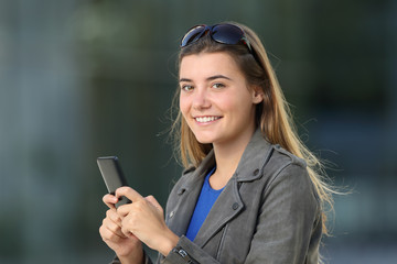 Fashion female using a phone and looking at you on the street