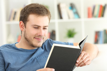 Man reading a paper book on a couch at home