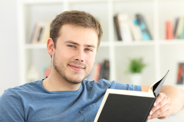 Man reading a book looking at you