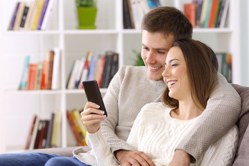 Couple watching media on a smart phone sitting at home