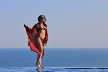Young woman relaxing at infinity pool at sunset. Lifestyle model vacation retreat