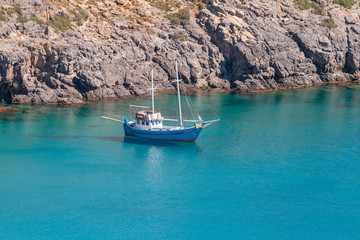 Small boat on blue sea near rocky coast on sunny day