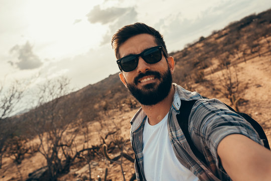 Man traveling with backpack hiking in desert. Travel lifestyle success concept. Man doing self portrait